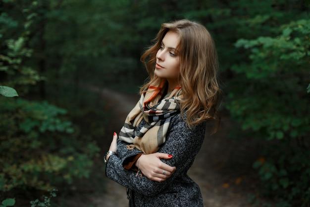 Elegante aantrekkelijke stijlvolle jonge vrouw in een luxe jas in een vintage sjaal staan op een loopbrug in het park