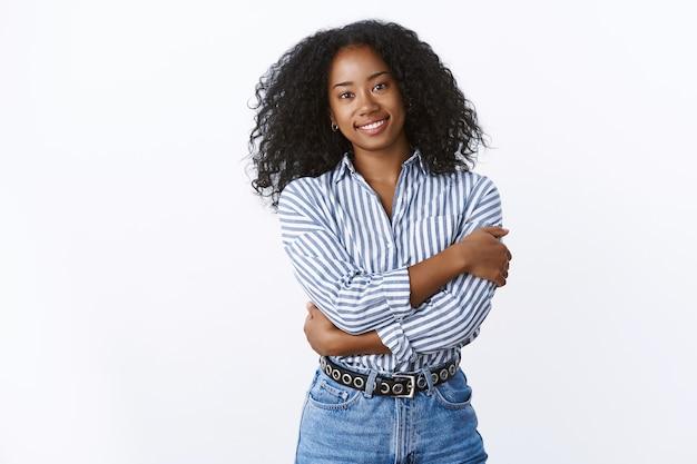 Elegante aantrekkelijke tedere vrouwelijke afro-amerikaanse jonge vrouw met krullend haar omhelst zichzelf met vrouwelijke sterke zachte tegelijkertijd, glimlachend dromerig knuffelen, draag kraag overhemd jeans witte muur