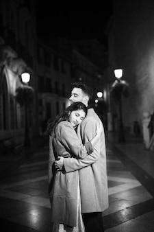 Elegante aantrekkelijke vrouw die met jonge man op straat bij nacht koestert