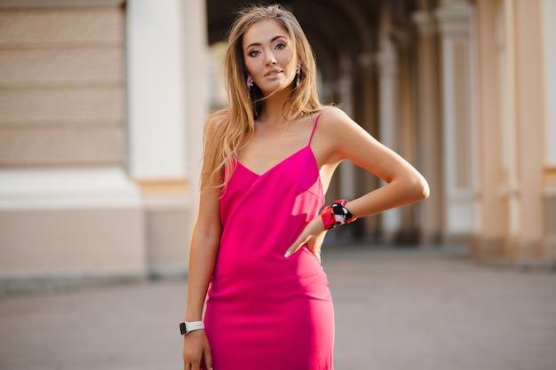 Elegante aantrekkelijke vrouw, gekleed in roze sexy zomerjurk wandelen in de handtas van de straatholding
