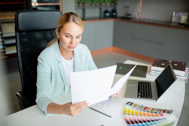Elegante accountant of makelaar die door financiële papieren kijkt terwijl hij op kantoor werkt