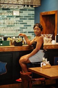 Elegante afrikaanse amerikaanse vrouw in een bar