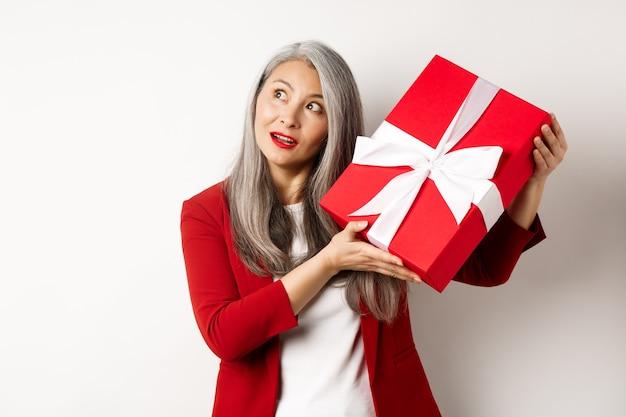 Elegante aziatische senior vrouw schudden geschenkdoos, proberen te raden wat erin aanwezig, staande op witte achtergrond. vakantie en viering concept.