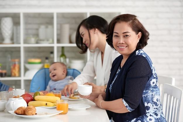 Elegante aziatische vrouw aan ontbijttafel met familie