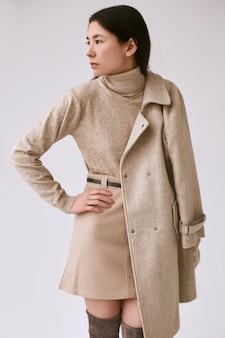 Elegante aziatische vrouw in modieuze wollen jas en klassieke rok