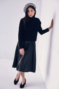 Elegante aziatische vrouw in modieuze zwarte rok en baret