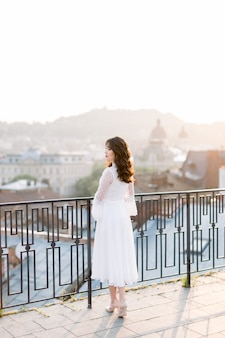 Elegante aziatische vrouw in witte kleding die zich op dakterras bevindt dat stad bekijkt