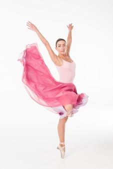 Elegante ballerina die op pointeschoenen dansen tegen witte achtergrond