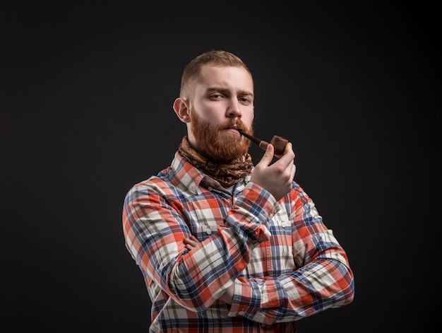 Elegante bebaarde man die rookpijp houdt