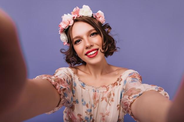 Elegante blanke meisje in cirkel van bloemen selfie maken en glimlachen. portret van ontspannen geïnspireerde dame met kort kapsel.