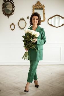 Elegante blanke vrouw met donker haar in groen pak poseert voor de camera en houdt een groot boeket witte bloemen vast