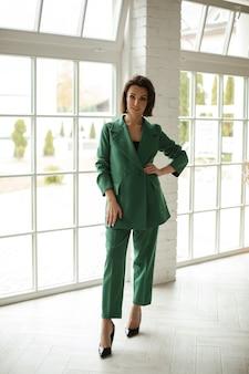 Elegante blanke vrouw met donker haar in groen pak poseert voor de camera in de grote lichte kamer