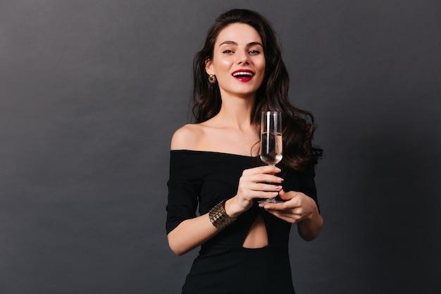 Elegante blauwogige meisje met rode lippenstift glimlacht en houdt glas champagne op zwarte achtergrond.
