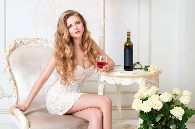 Elegante blonde dame met een glas wijn in het restaurant. mooie sexy jonge vrouw met lang haar perfect lichaam en mooie gezichtssamenstelling die avondjurk het drinken alcohol in licht luxebinnenland dragen.