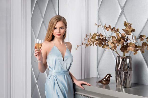 Elegante blonde dame met een glas wijn in het restaurant. mooie sexy jonge vrouw met lang haar perfect lichaam en mooie gezichtssamenstelling die blauwe avondjurk het drinken alcohol in luxe binnenland dragen.