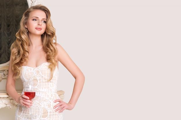 Elegante blonde dame met een glas wijn. mooie sexy jonge vrouw met lang haar perfecte lichaam en mooie gezicht make-up in avondjurk alcohol drinken in lichte luxe interieur. copyspace voor tekst.