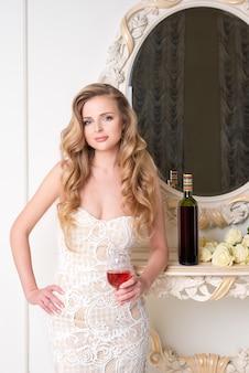 Elegante blonde dame met een glas wijn. mooie sexy jonge vrouw met lang haar perfecte lichaam en mooie gezicht make-up in avondjurk alcohol drinken in lichte luxe interieur