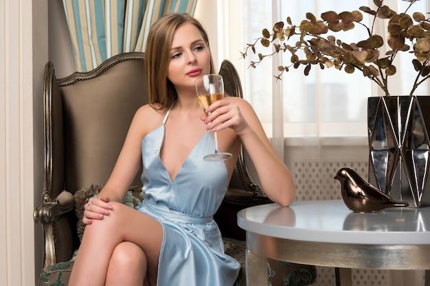 Elegante blonde dame met glas wijn in restaurant. mooie sexy jonge vrouw met lang haar perfect lichaam en mooi gezicht make-up dragen blauwe avondjurk alcohol drinken in luxe interieur.