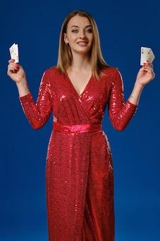 Elegante blonde dame met make-up, getatoeëerde hand, in rode pailletten jurk lacht, toont vier speelkaarten, poseren tegen blauwe achtergrond. gokken entertainment, poker, casino. detailopname.