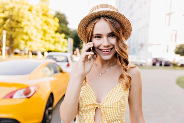 Elegante blonde meisje in vintage hoed praten over de telefoon in zomerweekend. leuk wit vrouwelijk model in gele kledij die van ochtendwandeling geniet.