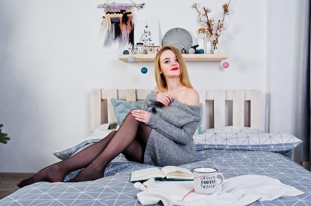Elegante blonde meisjesslijtage op warme uniformjaszitting op bed en gelezen boek met kop van hete koffie.