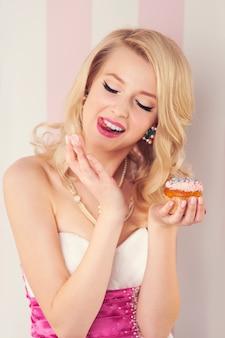 Elegante blonde vrouw die room van muffin eet