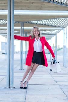 Elegante blonde vrouw die zich in de straat bevindt die rood jasje draagt
