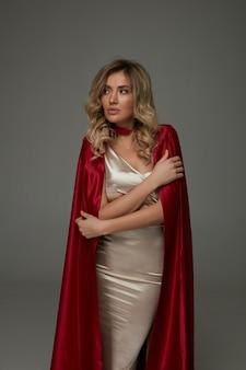 Elegante blonde vrouw in glanzende lange jurk en rode zijden cape