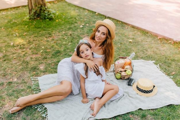 Elegante blonde vrouw ligt op een witte deken met een mand met appels in het weekend. openluchtportret van vrolijk meisje en haar moeder die van mooi weer in park genieten.