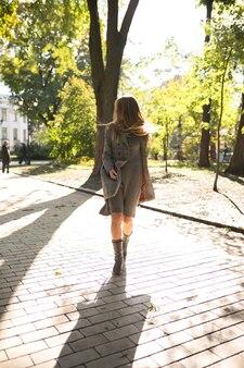 Elegante blonde vrouw met lang haar in gebreide jurk en warme jas wandelen in het park op zonnige dag
