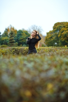 Elegante blonde vrouw met trui poserend in de botanische tuin