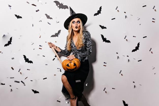 Elegante boze tovenaar met espstaak en pompoen. indoor portret van vrolijke vampier poseren met vleermuizen op muur.