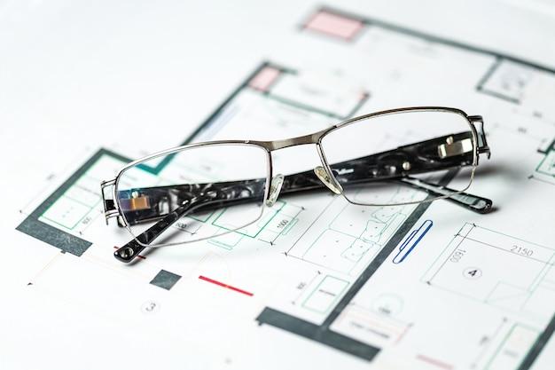 Elegante bril op een schematisch plan voor de reconstructie van de kamer