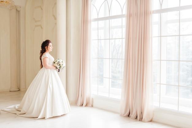 Elegante bruid die door een venster kijkt