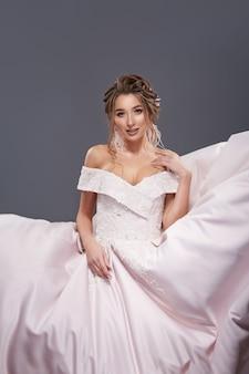 Elegante bruid die naar de camera kijkt en haar weelderige jurk aanraakt