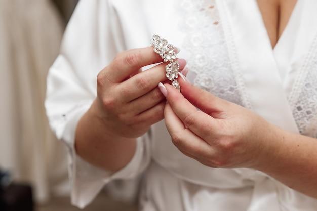 Elegante bruid die zilveren oorringen houdt