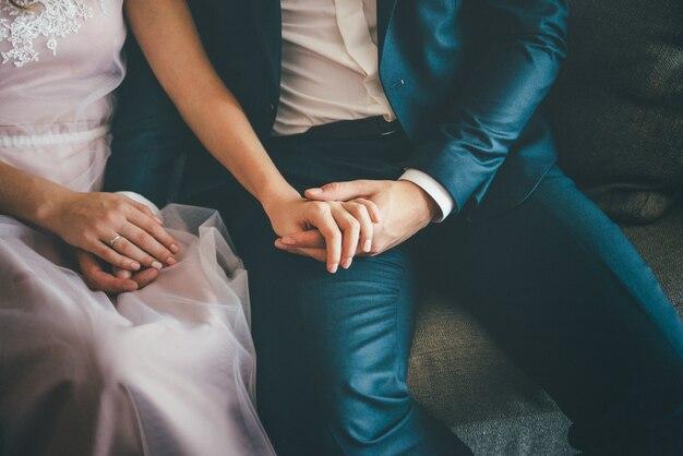 Elegante bruid en bruidegom zitten. hand in hand, close-up