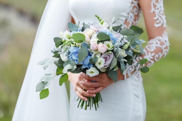 Elegante bruid in een trouwjurk met kant met bruids boeket bloemen