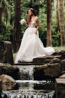 Elegante bruid in een witte jurk en handschoenen met een boeket staat bij een beek in het bos