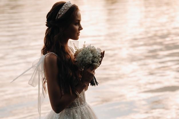 Elegante bruid in een witte jurk en handschoenen staat aan de rivier in het park met een boeket