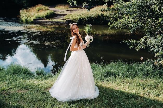 Elegante bruid in een witte jurk met een boeket in de natuur