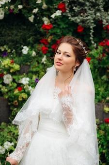 Elegante bruid staat op de achtergrond van een bloementuin in een elegante trouwjurk en bruidssluier met een diadeem