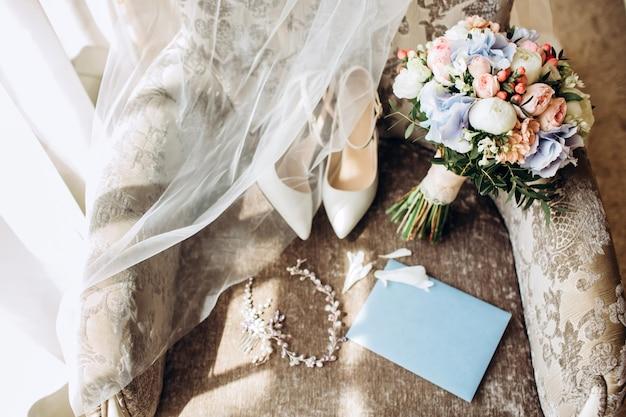 Elegante bruidsboeket met lint, trouwkaarten, verlovingsringen en schoenen voor de bruid op een stoel.