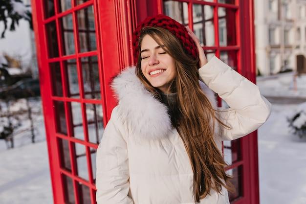 Elegante bruinharige vrouw poseren met romantische glimlach en gesloten ogen tijdens de winter in engeland. openluchtportret van dromerige glimlachende vrouw in rode wollen baret die van fotoshoot dichtbij telefooncel geniet.