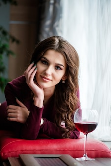 Elegante brunette dame in rode avondjurk met glas rode wijn in restaurant