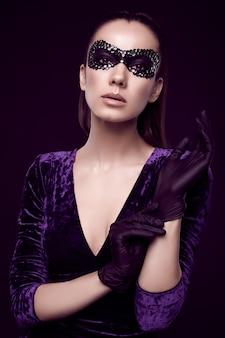 Elegante brunette vrouw in mooie paarse jurk en pailletten masker handschoen omhoog