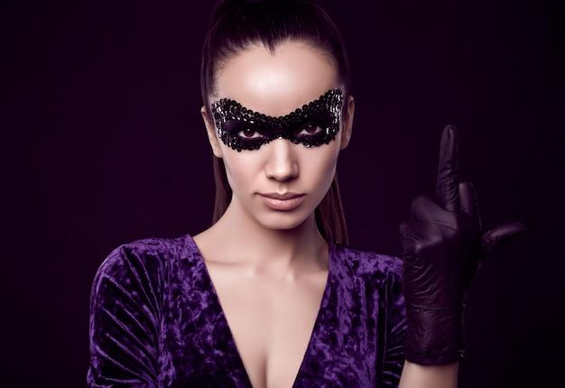 Elegante brunette vrouw in paarse jurk en pailletten masker toont middelvinger