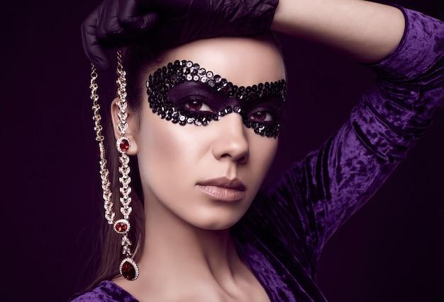 Elegante brunette vrouw in prachtige paarse jurk, pailletten masker en zwarte handschoenen