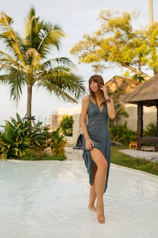 Elegante brunette vrouw in sexy jurk poseren in stijlvol strandrestaurant in aziatische stijl. volledige lengte.