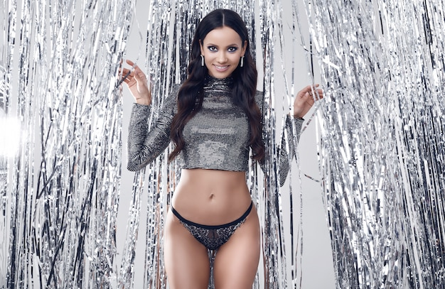 Elegante brunette vrouw met perfect lichaam in luxe pailletten top